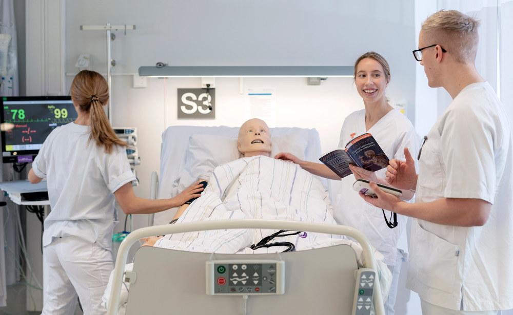 Sykepleierstudenter med pasentsimulator i seng Bilde