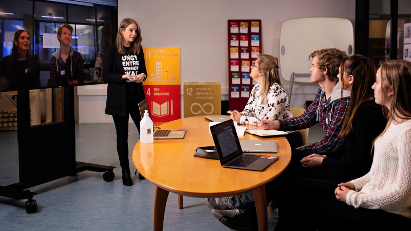 Woman talking in front of three students. Photo