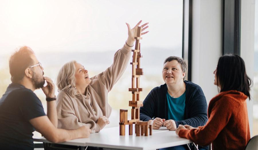 Fire mennesker sitter rundt et bord og ser på et tårn laget av klosser. foto.