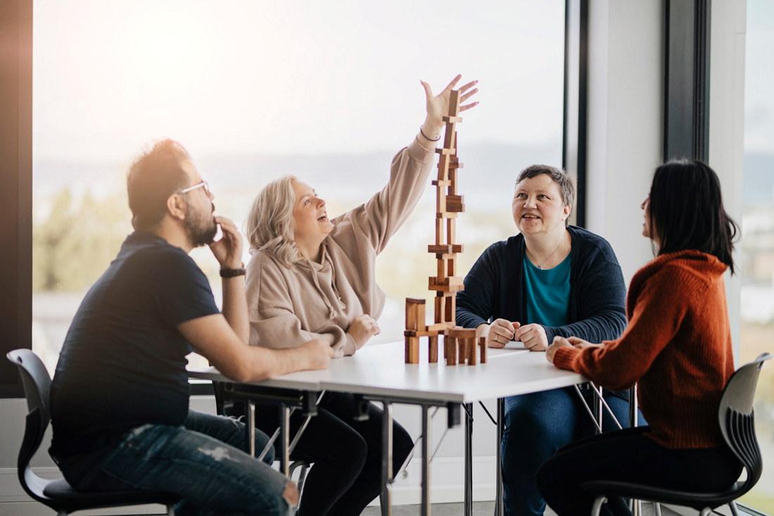 Fire studenter sitter ved et bord og spiller et spill
