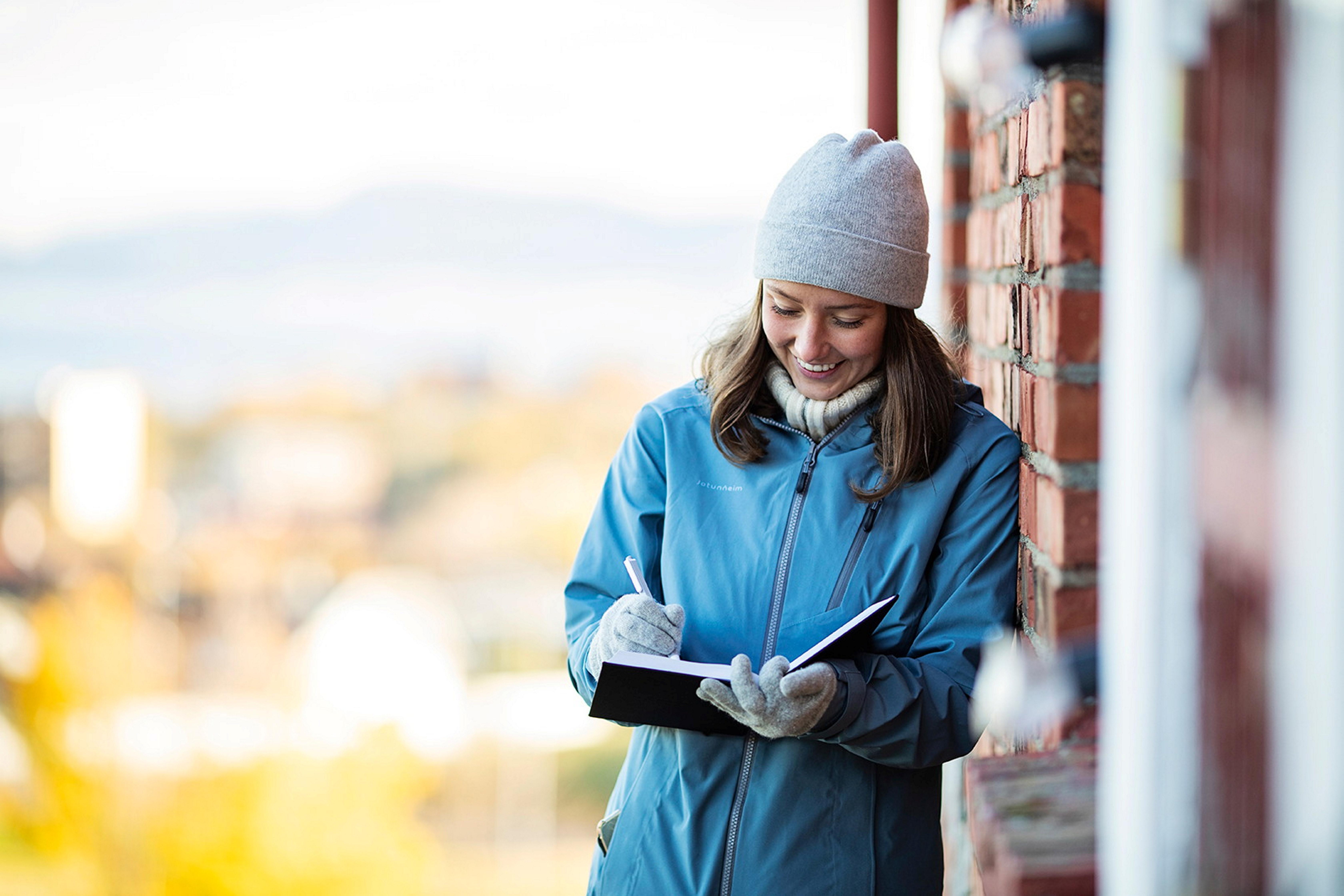 Student som smiler og holder en bok utendørs. Bilde