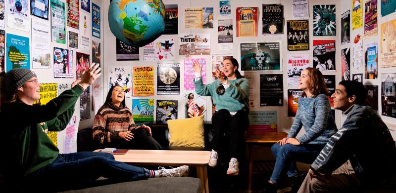 Studenter som sitter og kaster en globusball. Bilde